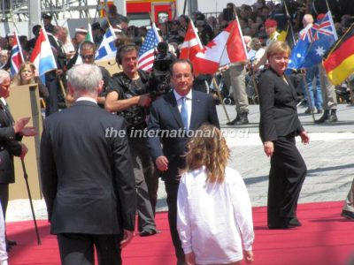 Heads of state (chancelor Angela Merkel here, leaving the red carpet) took turns greeting President François Hollande and WWII D-Day veterans